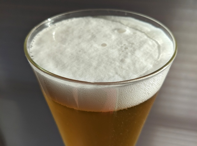 Close-up of pilsner beer foam in conical glass