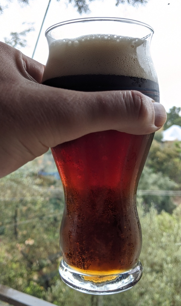glass of beer held by hand, with the beer having a brown color, quite lear, and a tan head