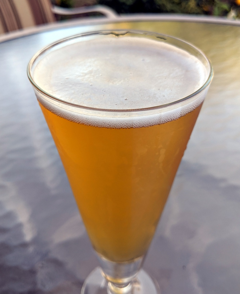 golden beer with white head in conical pilsner glass