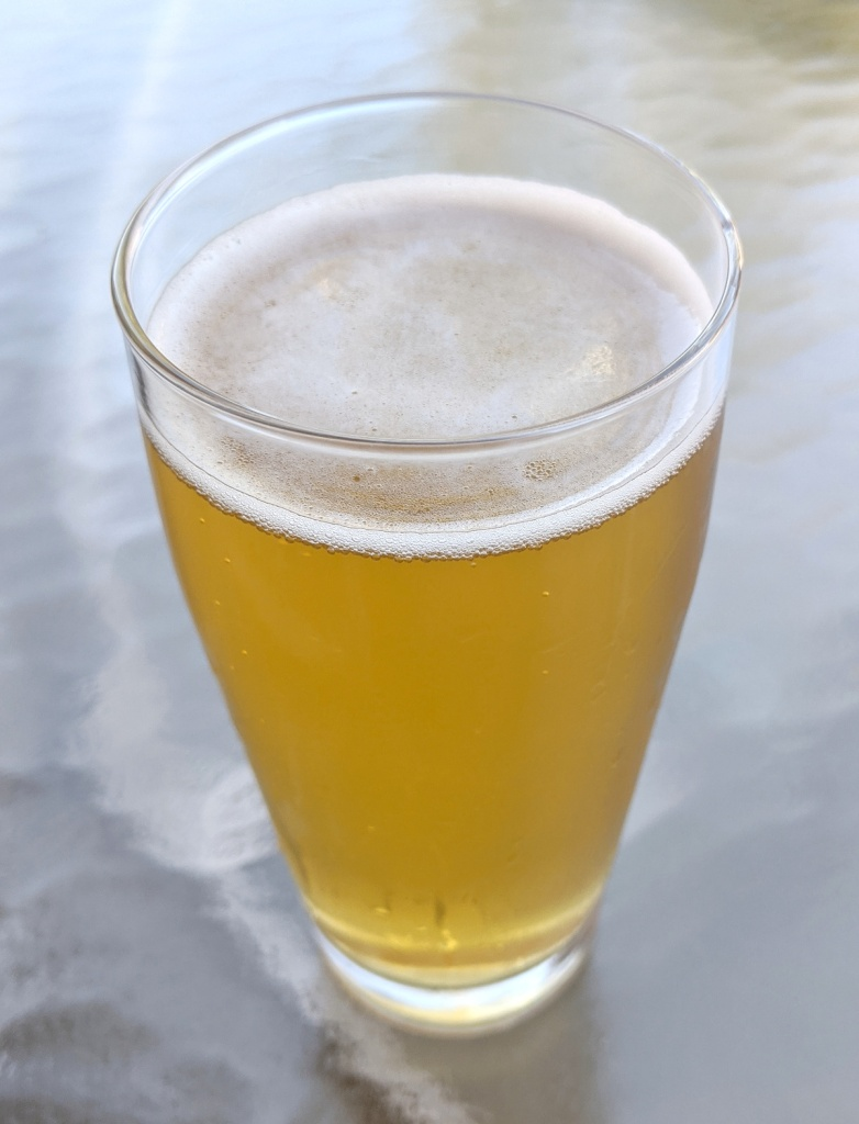 pale gold beer with thin white head in clear glass, sitting on glass patio table