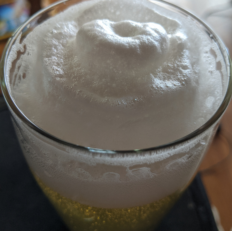 creamy white beer head, in a glass atop a pale yellow lager beer