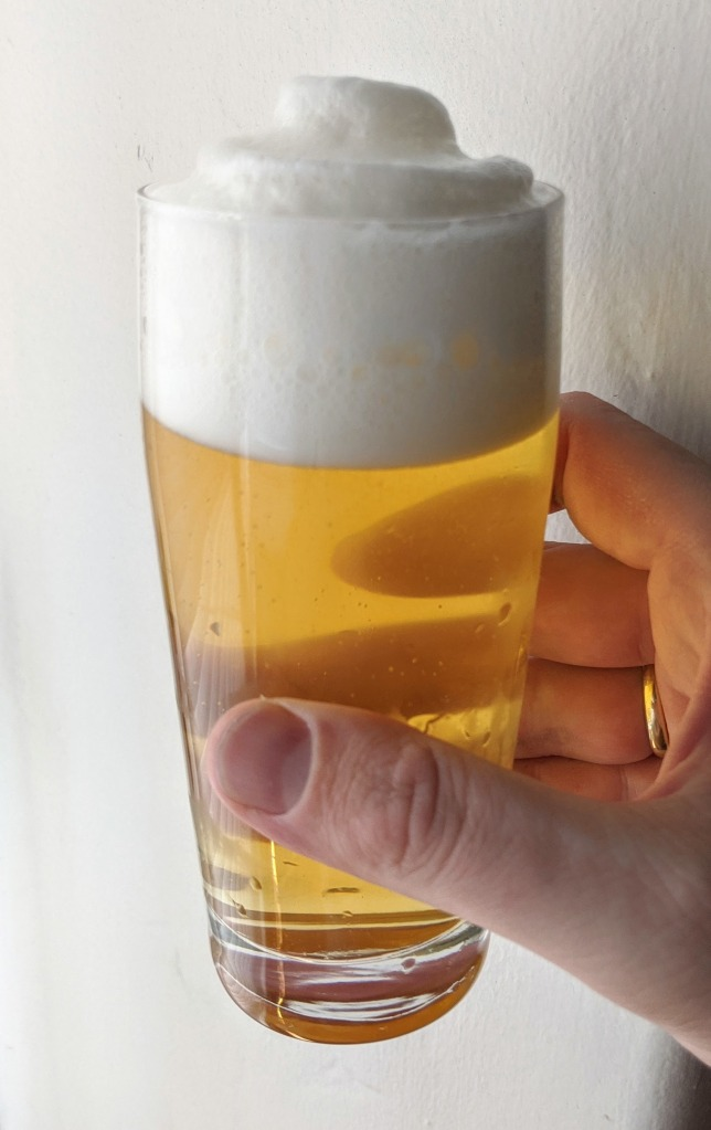 golden beer with frothy white head in clear glass, held by hand
